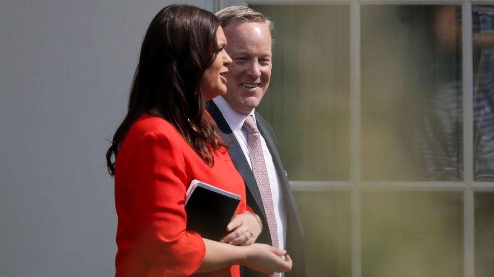 Sarah Sanders and Sean Spicer walk together in 2017