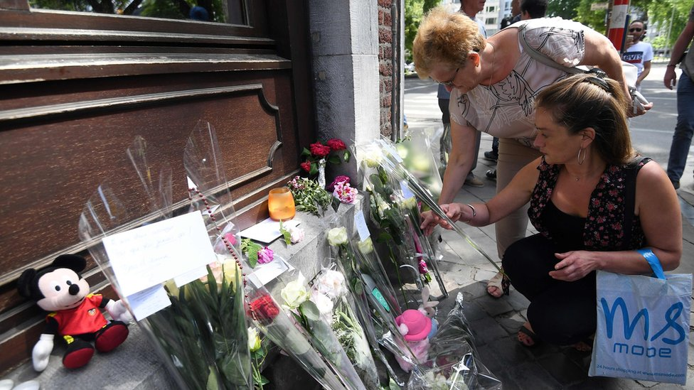 People pay tribute to the victims of the Liege's shooting on May 30, 2018, in Liege at a makeshift altar situated where the two policewomen were killed during the attack the day before.