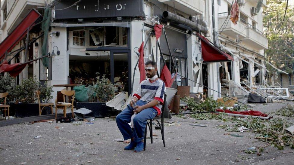 Un hombre se sienta frente a un restaurante destruido por la explosion el 5 de agosto de 2020