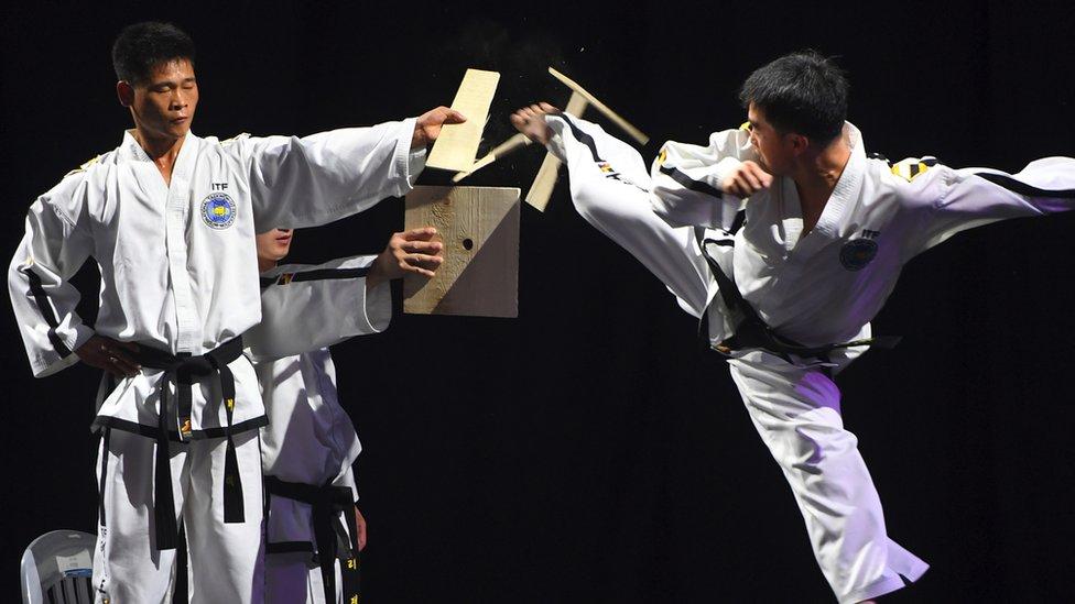 A man kicks through a wooden board during a taekwondo demonstration