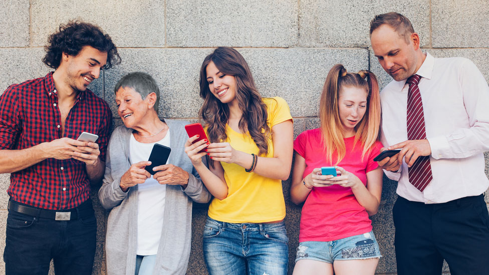 Cinco personas de diferentes edades con sus celulares