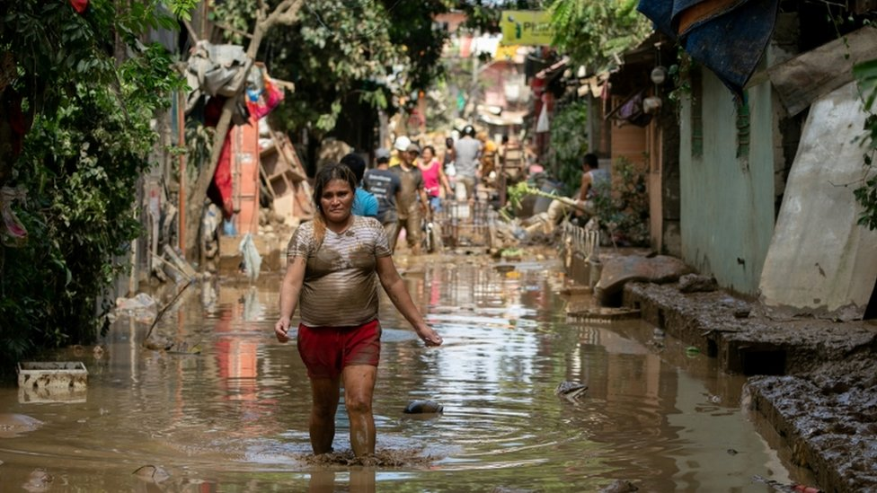 A woman wades through muddy floodwater following Typhoon Vamco, in San Mateo, Rizal province
