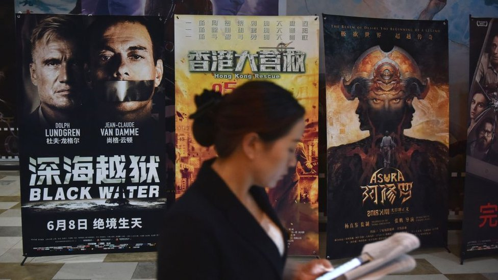 A woman looks at her mobile phone near movie posters outside a theatre in Beijing on May 23, 2018.