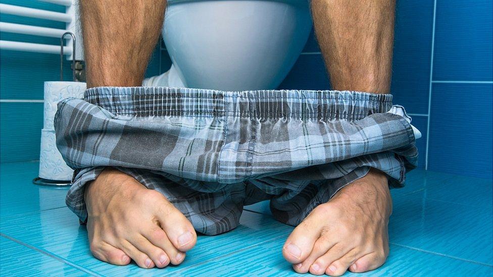 Hombre sentado en el inodoro