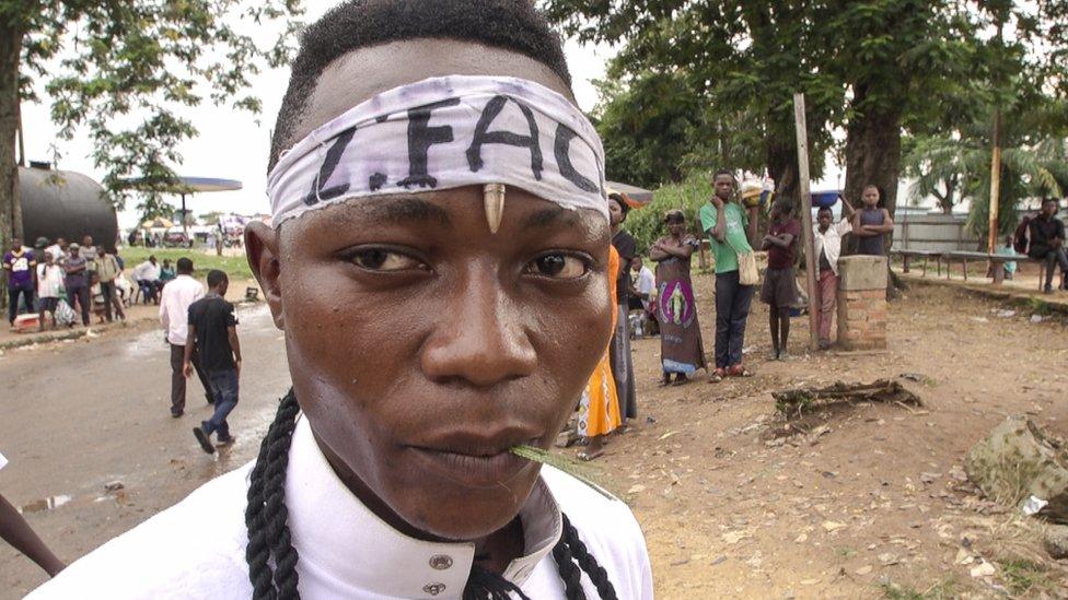 Kamuina member - Militia member standing in Kananga town.