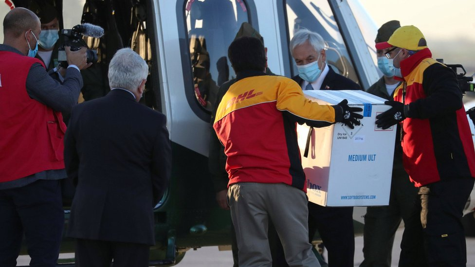 "Chile""s President Sebastian Pinera looks as workers carry the first batch of the Pfizer-BioNTech COVID-19 vaccine to a helicopter, as the coronavirus disease (COVID-19) outbreak continues, at the Santiago International Airport, in Santiago, Chile December 24, 2020. REUTERS/Ivan Alvarado"
