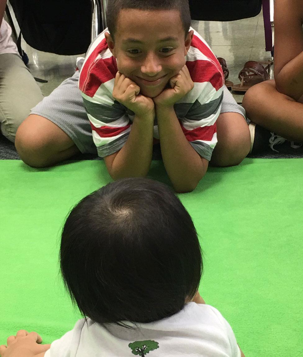 Un niño le sonríe a un bebé durante un programa de Roots of Empathy.