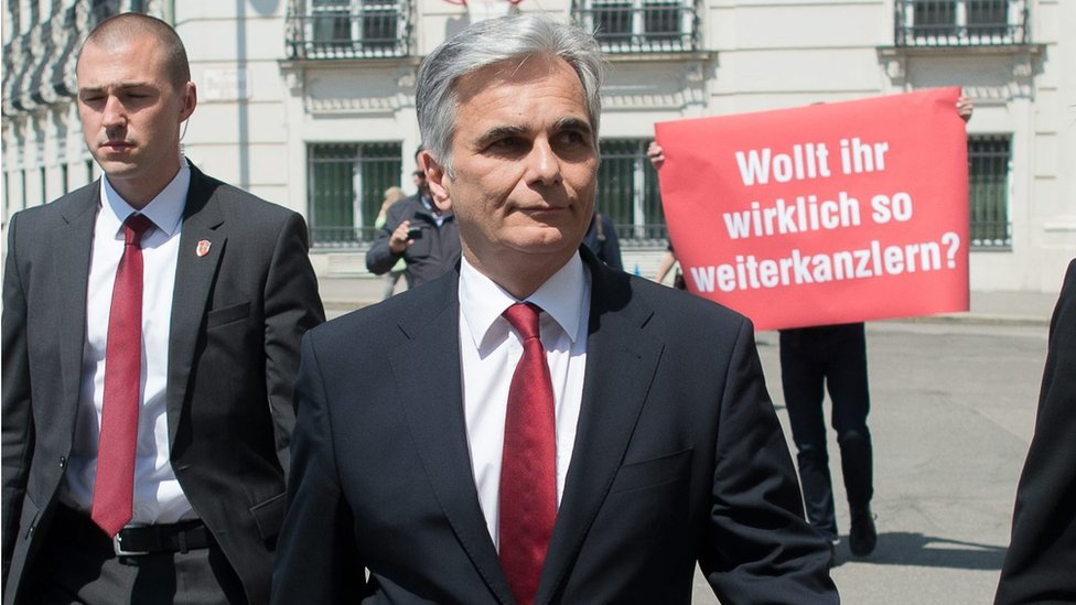 A protester holds up a placard calling for Werner Faymann's resignation (9 May)
