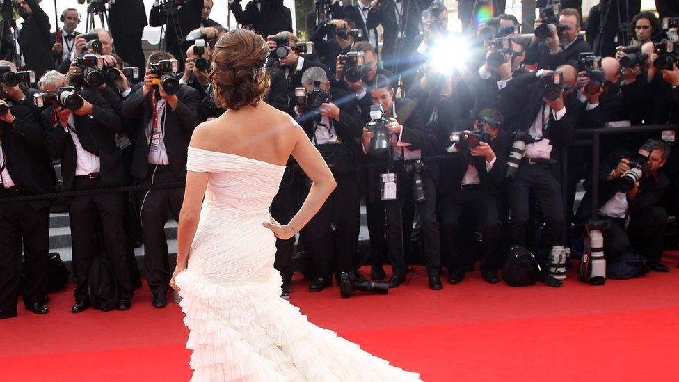 Paparazzi fotografiando a una celebridad en una alfombra roja.
