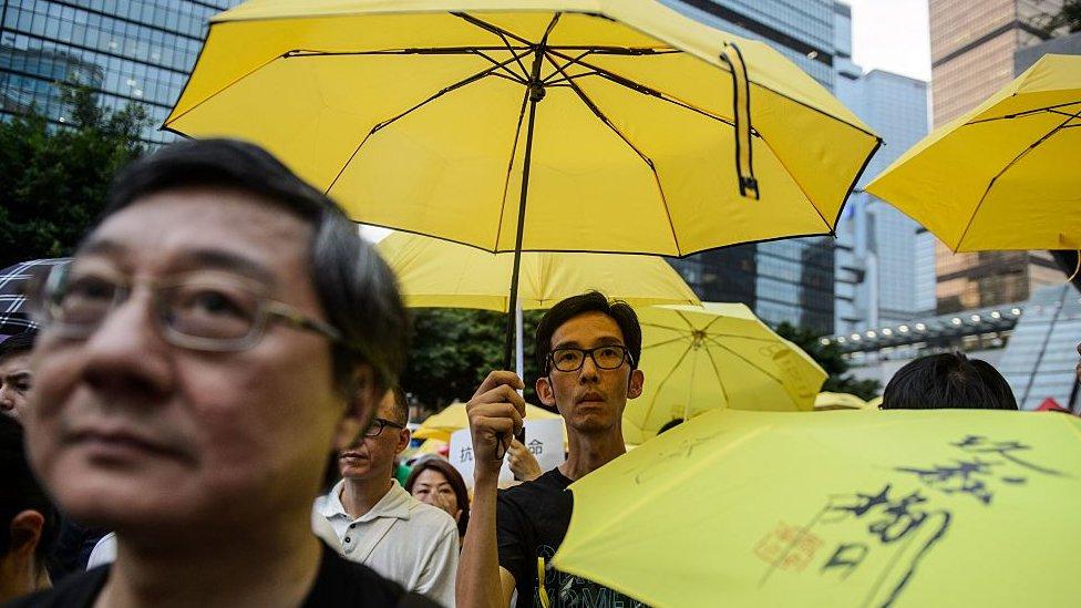 Activists hold yellow umbrellas, a symbol of the pro-democracy movement