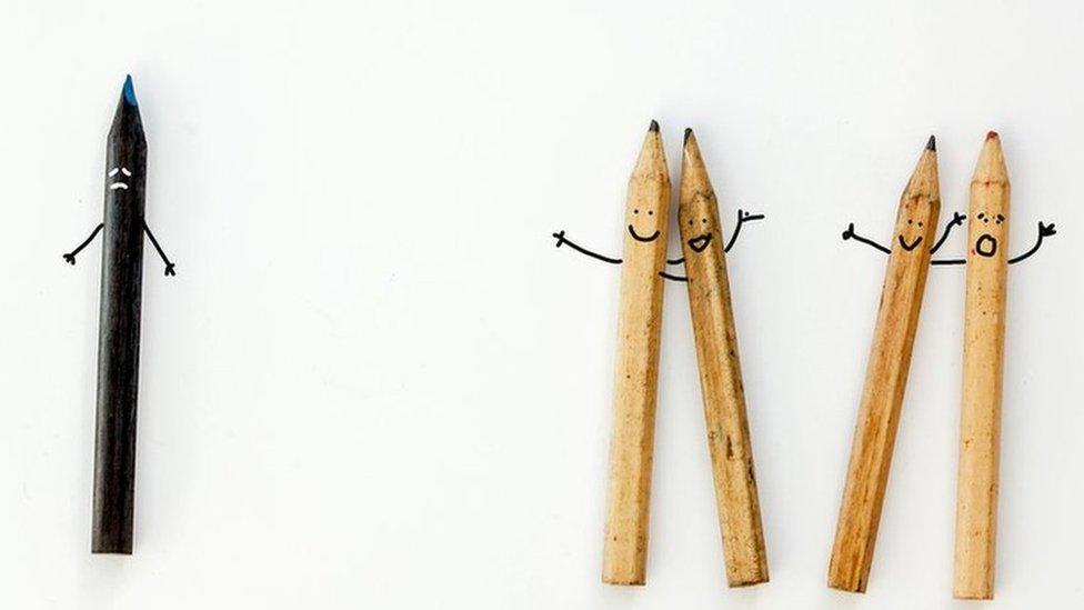 Un lápiz negro separado de otros cuatro.