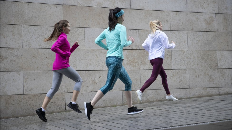 Rear view of three woman jogging on footpath along side a wall. - stock photo
