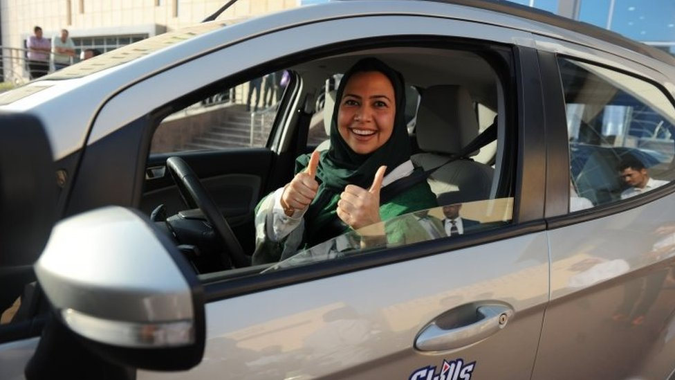 Woman behind wheel of car with thumbs up
