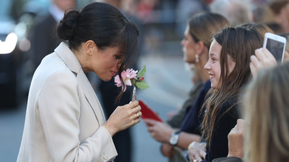 Meghan handed a flower by a girl