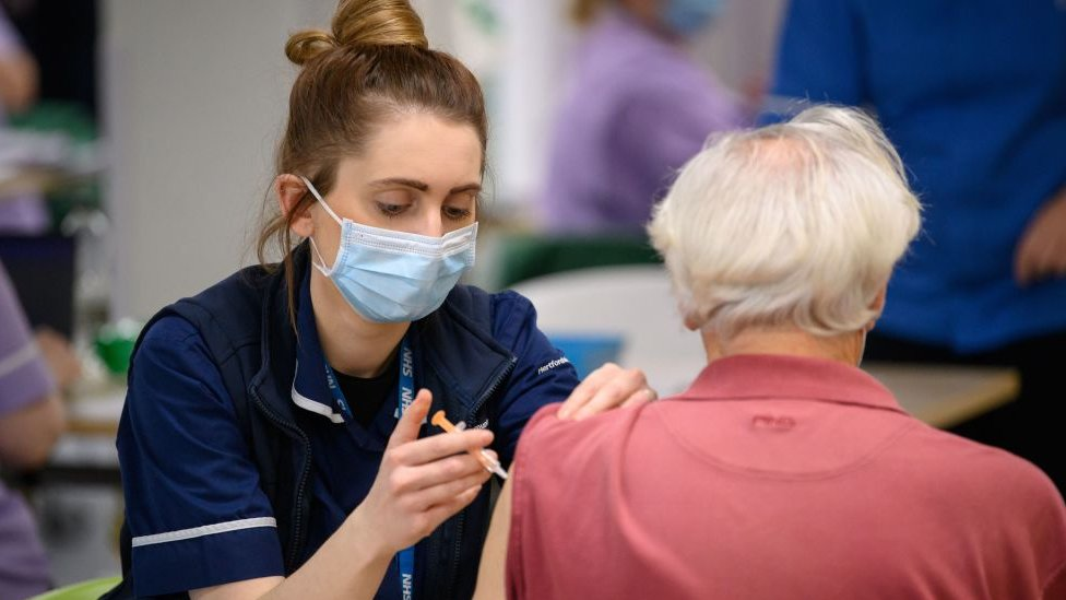 A member of the medical team administers a coronavirus Covid-19 vaccine shot at the NHS vaccination centre in Robertson House in Stevenage, north of London on January 14, 2021