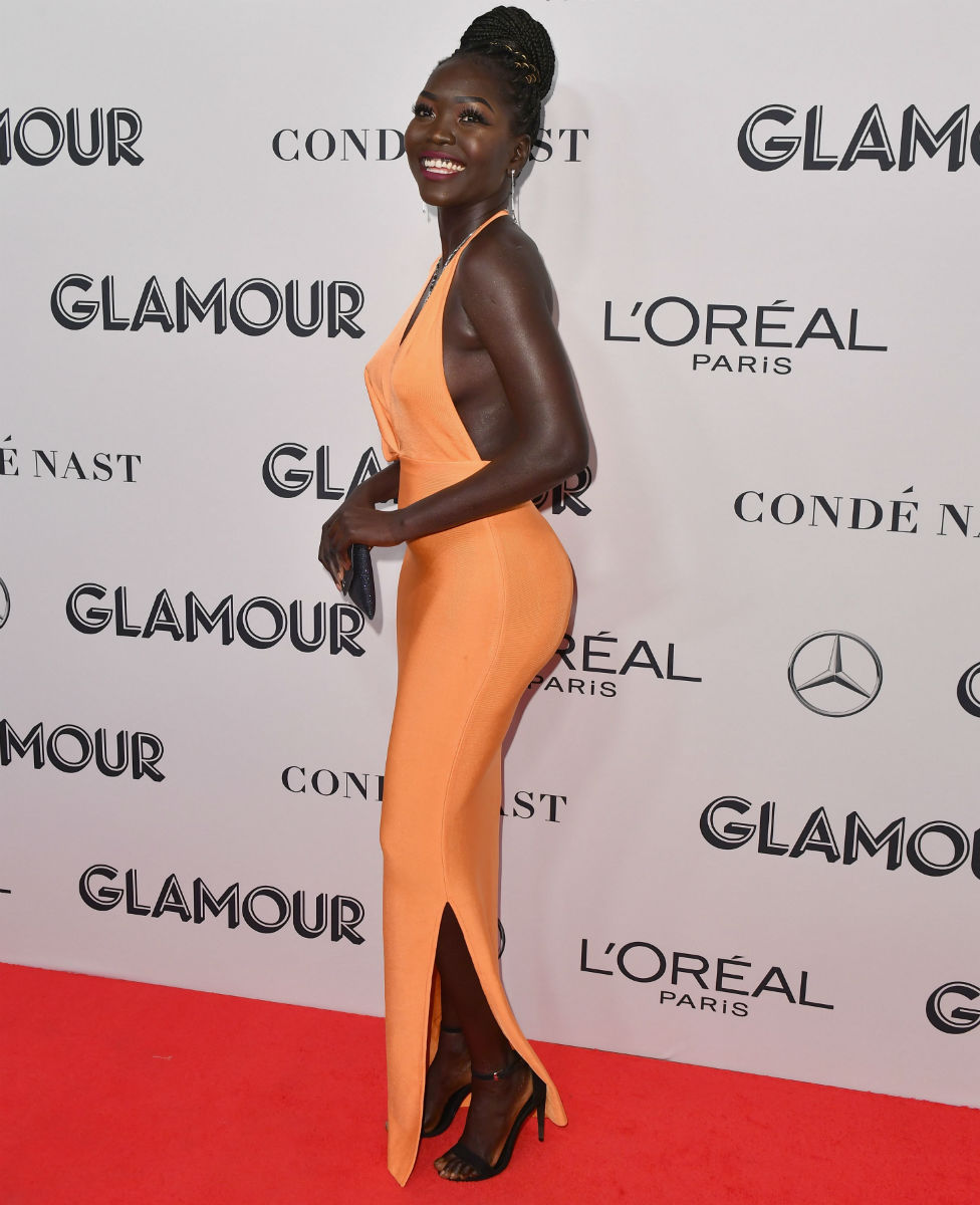 South Sudanese model Nyakim Gatwech, dressed in orange, smiles for the cameras as she walks the red carpet at the Glamour Women of the Year awards