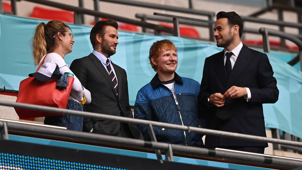 Cherry Seaborn, wife of Ed Sheeran, David Beckham and Ed Sheeran are seen in the stands at Wembley stadium