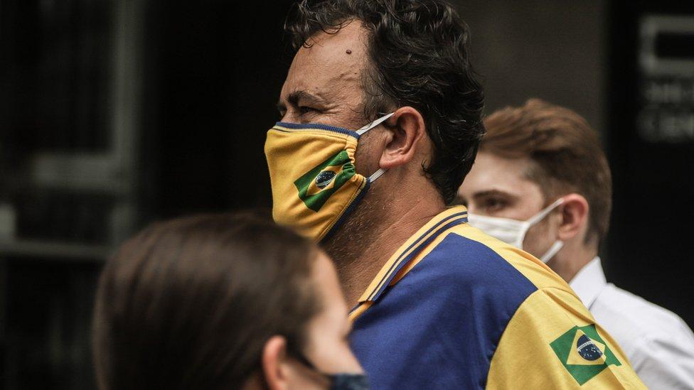 Un hombre en Brasil lleva una mascarilla con la bandera de su país.