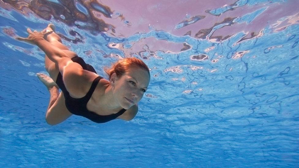 Mujer bajo el agua con los ojos abiertos.
