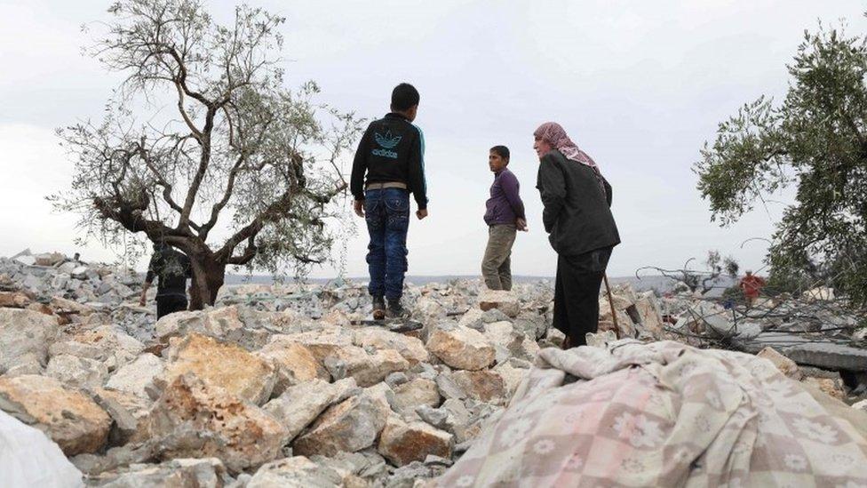 Sirios rondando los escombros que quedaron tras la operación contra Al Baghdadi.