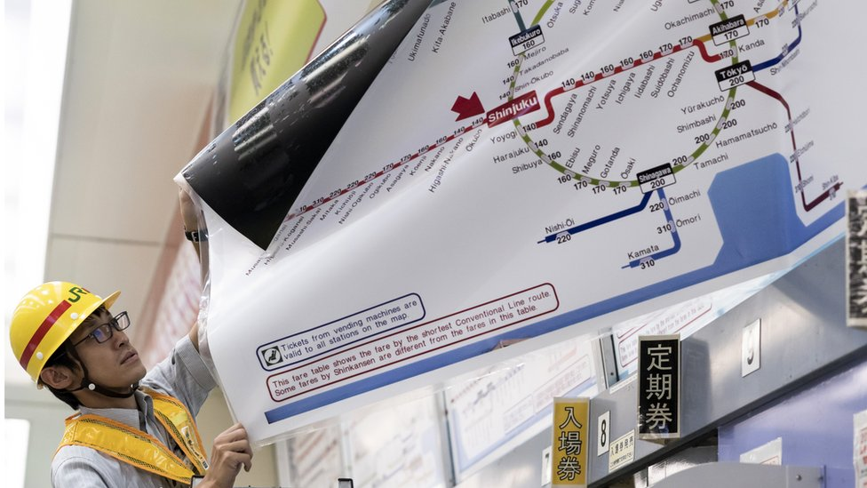 Man replaces a map with train fares