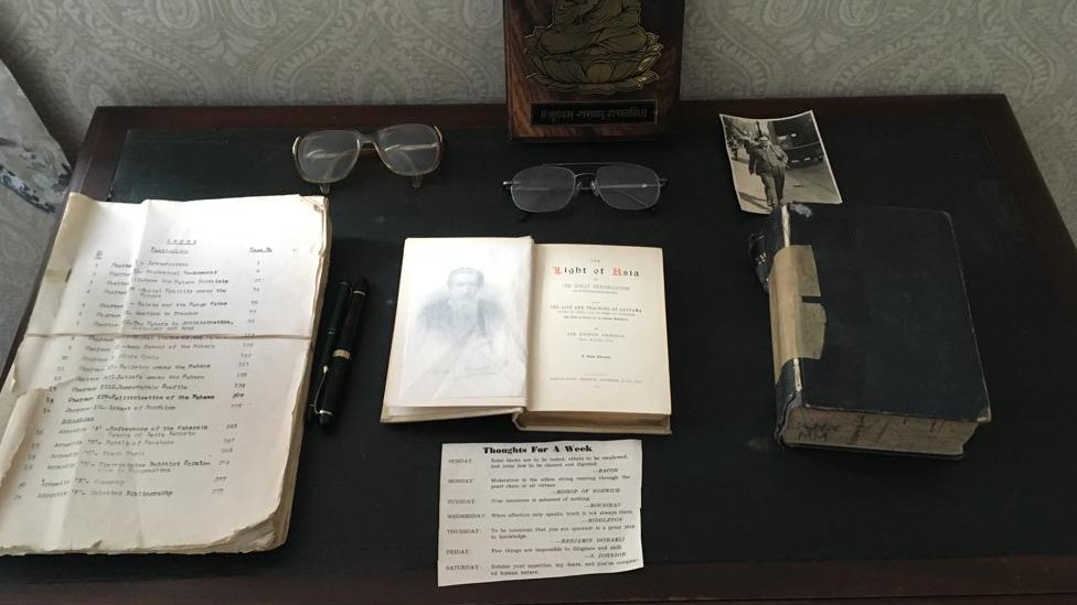 A desk with replica books and a pair of glasses