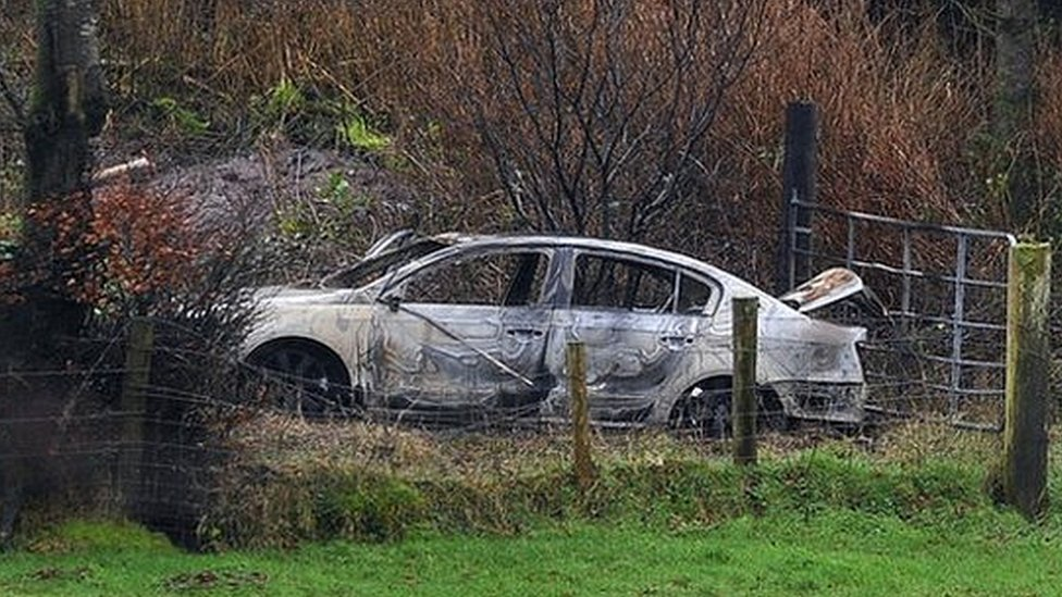 A burnt-out car suspected to have been used after the killing