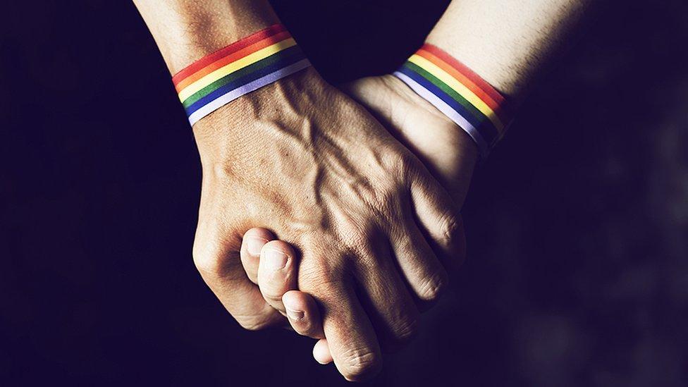 Manos con pulseras con los colores del arcoiris.