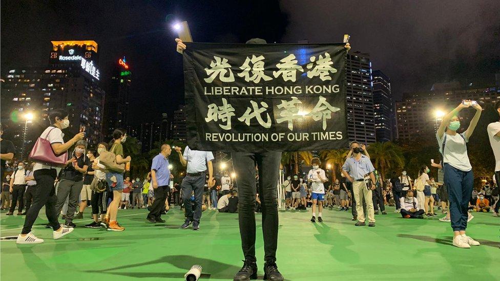 """香港維多利亞公園足球場上一位參與「六四""""集會人士高舉「反修例」標語(4/6/2020)"""