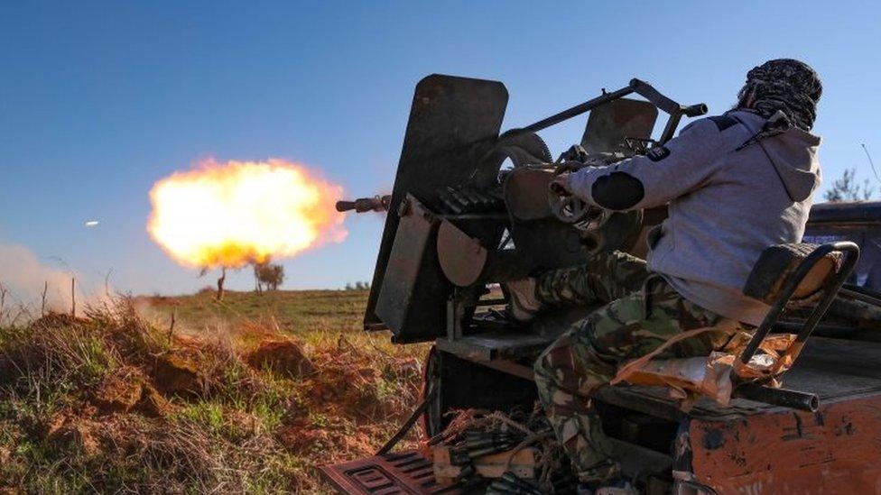 Un combatiente sirio respaldado por Turquía dispara un arma desde un camión en Idlib.