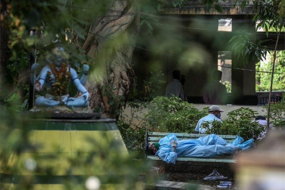 Un hombre vestido en traje protector descansa en un banco antes de realizar los ritos fúnebres a un familiar víctima de covid-19, en Bombay. 13 de abril de 2021