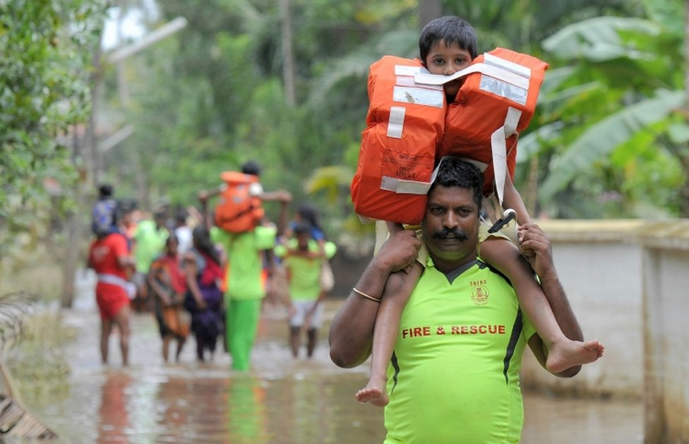 Fire service personnel carry children on their shoulders through floodwaters during a rescue operation in Annamanada village, in Kerala