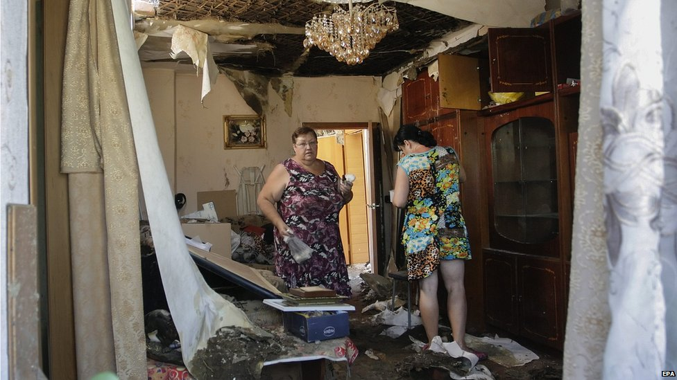 Local people react as they return to home that was damaged during a shelling, in Donetsk, Ukraine, 2 August 2015