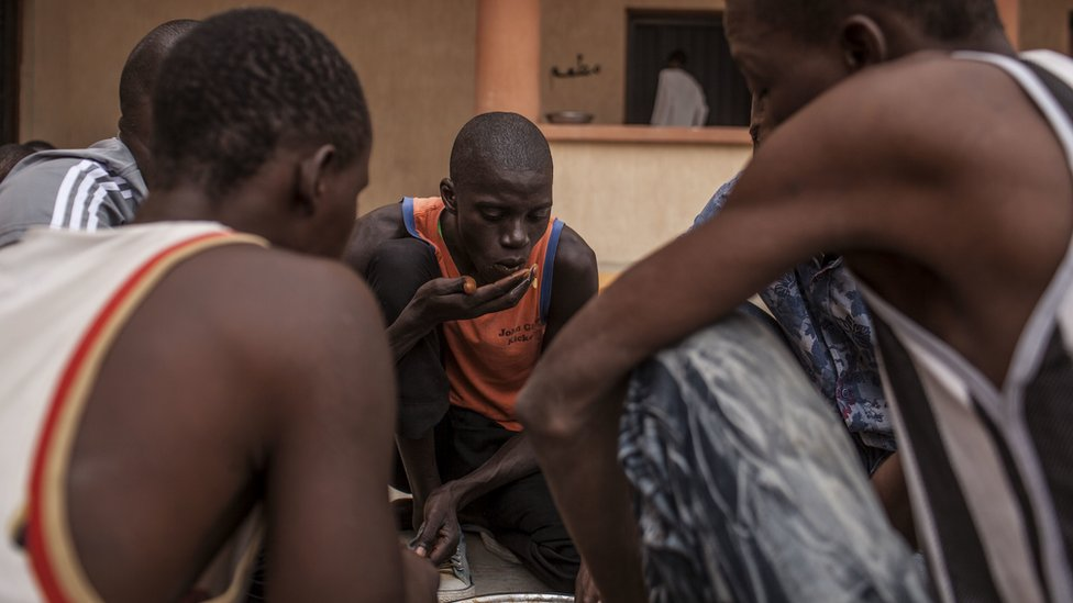 A migrant from Senegal, and other detainees eat in the courtyard of a detention centre for migrants near Misrata, Libya - Sunday 25 September 2016