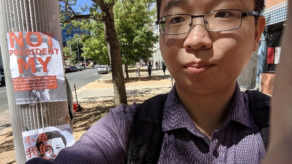 """Wu Lebao stands next to a poster saying """"not my president"""" at the Australian National University"""