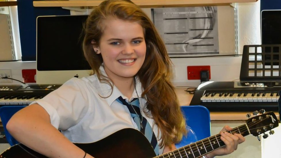 Daisy Clark with her guitar at school