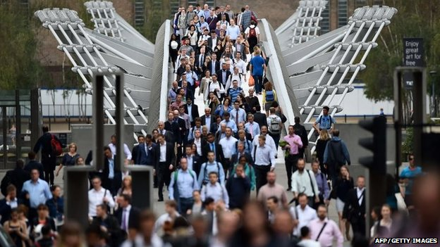 Commuters cross the river Thames on the Millennium footbridge during rush hour