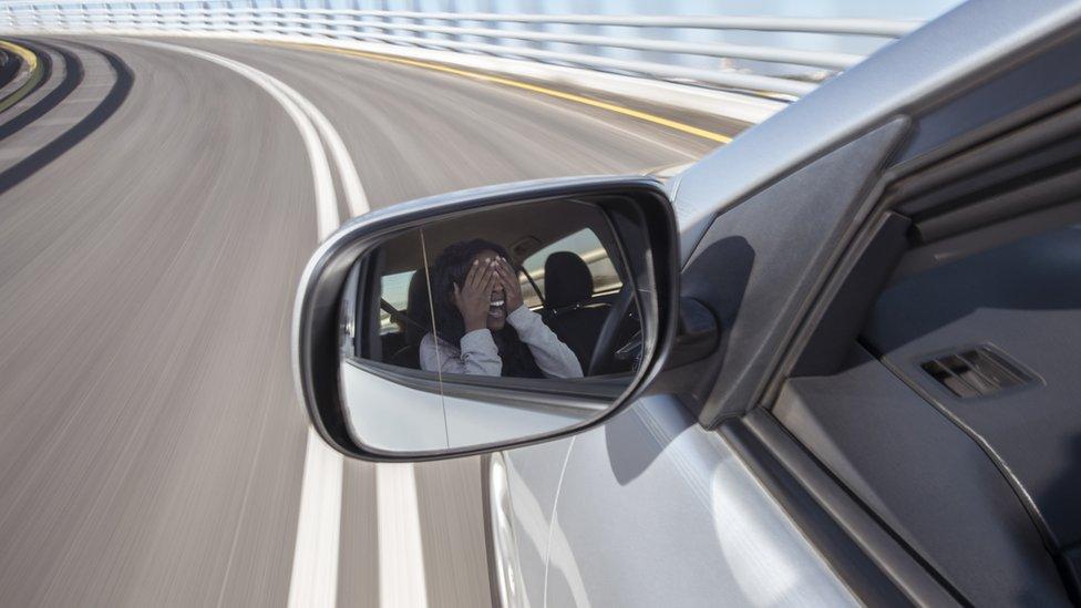 Mujer tapándose los ojos en un coche que circula a gran velocidad.