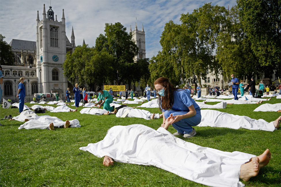 Protesters lie on the ground pretending to be dead with white sheets over them, with doctors looking on