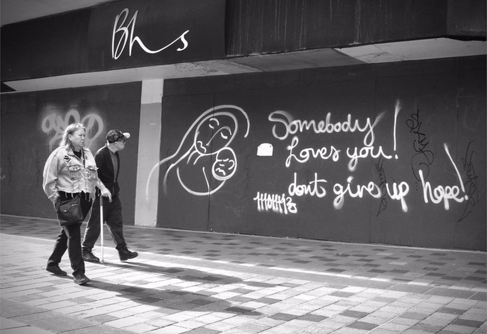 Two people walk down a high street and look at graffiti on a shop wall
