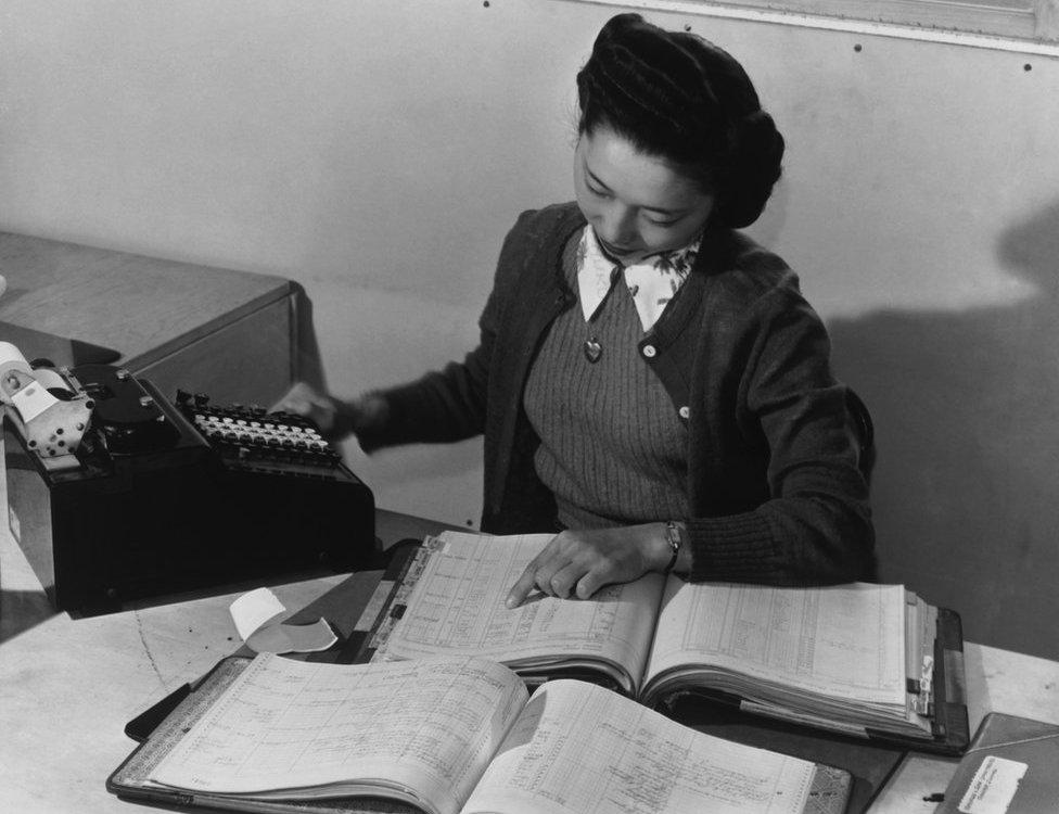 Contadora Teruko Kiyomura actualizando manualmente varios libros de contabilidad en 1943.