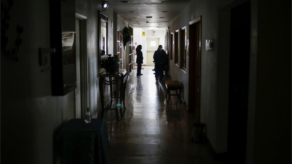 Personas en un corredor de un edificio sin luz