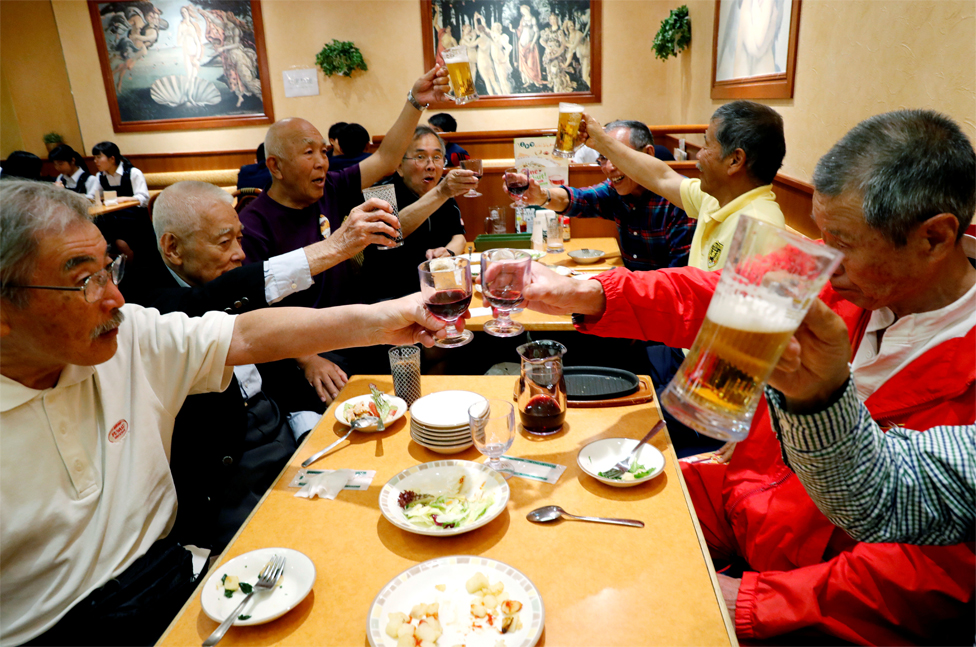 Members of Tokyo's Fuwaku Club raise their glasses in a restaurant