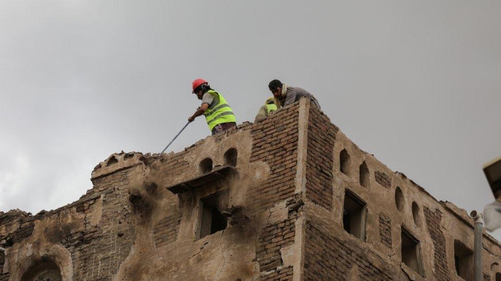 عمال يهدمون مبنى أضرت به الأمطار.