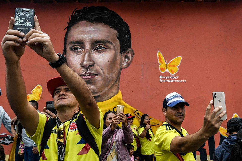 People make selfies with a mural depicting Colombia's Tour de France winner Egan Bernal after arrival in his hometown Zipaquira, Cundinamarca, Colombia