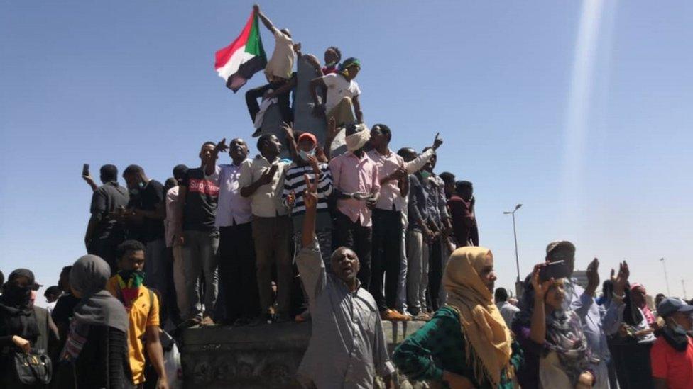 متظاهرون يلوحون بالعلم السوداني أمام مقر الجيش في السادس من إبريل/نيسان