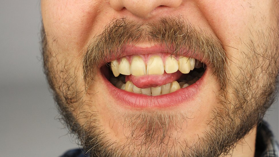 Boca de hombre con lengua y dientes.