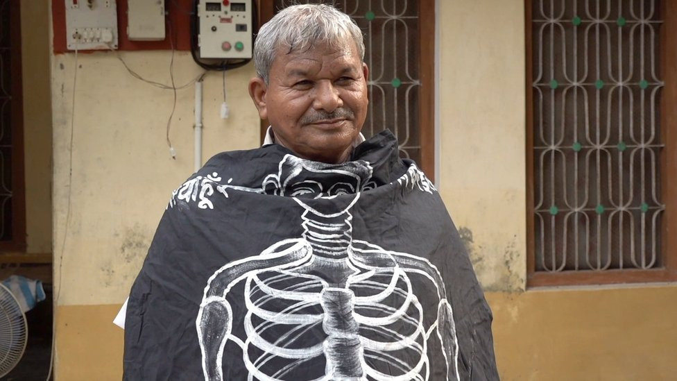 Lal Bihari Mritak wrapped in an Association of the Living Dead banner