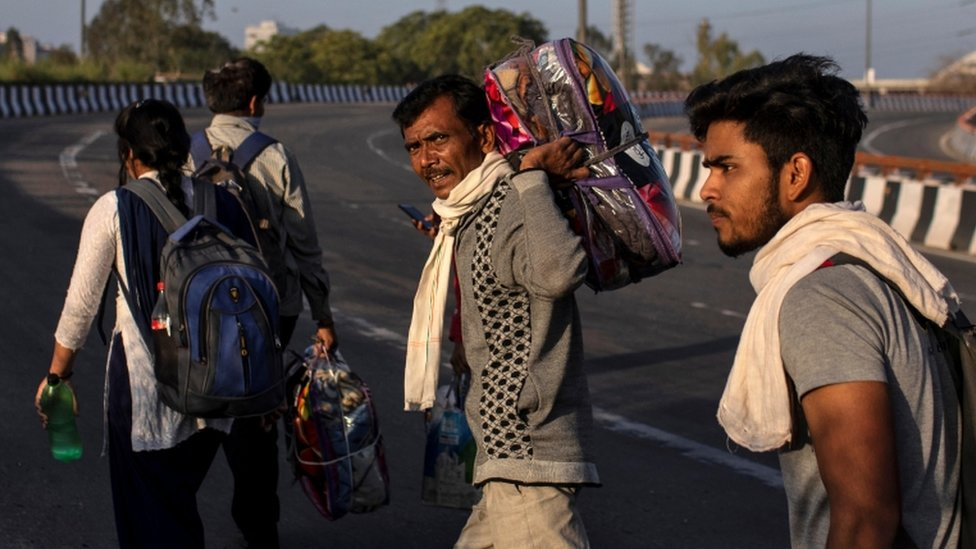Un grupo de hombres retorna a sus hogares en medio del cierre de India por la pandemia.