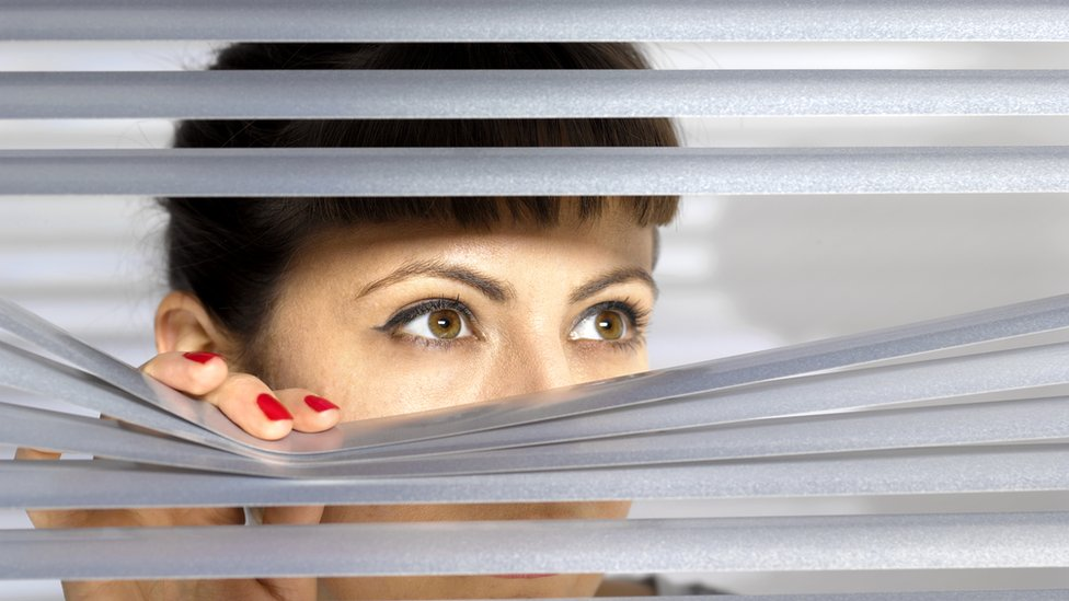 Mujer mira por una ventana